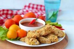 De goudklompjes van de kip met tomatensaus Stock Afbeeldingen
