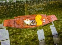 De goudsbloem en de witte lotusbloem met kaars in mini houten boot op duidelijk water, Thais mensengebruik voor weren pech af Stock Foto