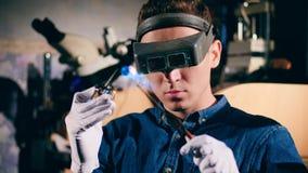 De goudsmid in een professionele juwelenworkshop in een masker brandt metaalring, die in een juwelenworkshop werken stock videobeelden