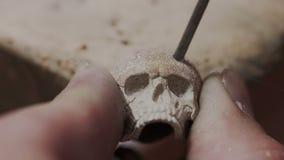De goudsmid maakt tot ongebruikelijke juwelen ringvormige schedel Hij borengaten in het metaal Professionele juwelenvakman detail stock videobeelden