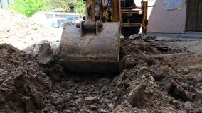 De graafwerktuigemmer giet grond Het loodgieterswerk van het reparatiewerk stock footage