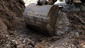 De graafwerktuigemmer giet grond Het loodgieterswerk van het reparatiewerk stock videobeelden