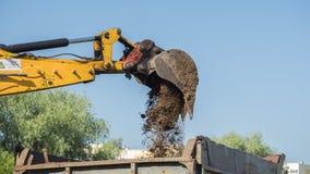 De graafwerktuigemmer giet grond in de vrachtwagen stock afbeelding
