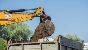 De graafwerktuigemmer giet grond in de vrachtwagen royalty-vrije stock afbeeldingen