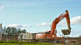 De graafwerktuigemmer laadt zware vrachtwagen met grond stock video
