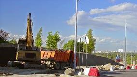 De graafwerktuigemmer laadt zware vrachtwagen met grond stock videobeelden