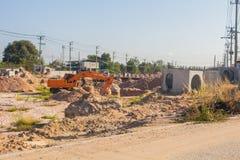 De graafwerktuigen graven grond aan opstelling een grote drainagepijp dicht bij de weg in het stadsgebied stock fotografie