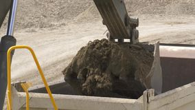 De graafwerktuiglepel laadt een stortplaatsvrachtwagen stock video