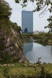 De gracht van Osaka Castle met moderne gebouwen in de afstand Stock Foto