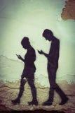 De graffiti met het beeld van jongen en meisje met mobiele telefoons drawed op de muur in een centrum van Praag royalty-vrije stock fotografie