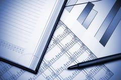 De grafiek, de pen en het notitieboekje van de voorraad. Royalty-vrije Stock Afbeeldingen