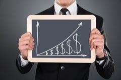 De Grafiek en de Dollartekens van zakenmanholding slate with Royalty-vrije Stock Fotografie