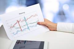 De grafiek van de onderneemsterholding in haar hand De digitale tablet is Stock Afbeeldingen
