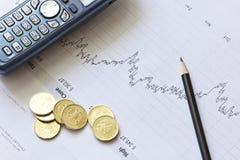 De grafiek van de voorraad met een potlood, een telefoon en muntstukken Royalty-vrije Stock Foto's