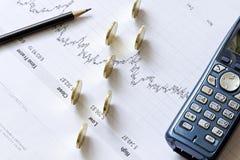 De grafiek van de voorraad met een potlood, een telefoon en muntstukken Stock Afbeeldingen
