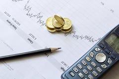 De grafiek van de voorraad met een potlood, een telefoon en muntstukken Stock Foto's