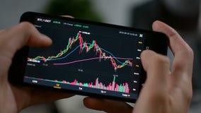 De grafiek van de de prijsgrafiek van Bitcoincryptocurrency op het mobiele telefoonscherm, de voorspellingsconcept van de cryptoc stock video