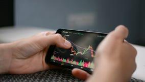 De grafiek van de de prijsgrafiek van Bitcoincryptocurrency op het mobiele telefoonscherm, de voorspellingsconcept van de cryptoc stock videobeelden
