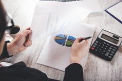 De grafiek van de vrouwenhand met calculator stock foto