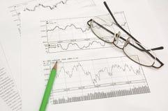 De grafieken, het potlood en de glazen van de voorraad Royalty-vrije Stock Afbeelding