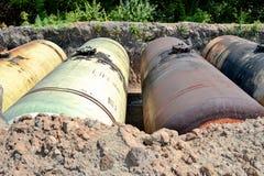 De grands réservoirs en métal sont enterrés dans la terre dans l'entrepôt de production photographie stock