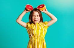 De grapefruit van de meisjesholding met afkeeruitdrukkingen stock foto