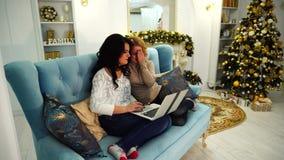 De grappige aardige vrienden brengen prettige avond bij computer door, zitting op laag in heldere woonkamer met feestelijke open  stock videobeelden