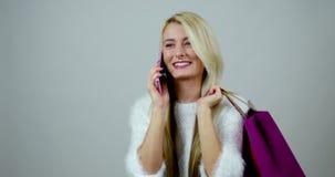De grappige antwoorden van het maniermeisje op een vraag op haar mobiel apparaat en houdt het winkelen pakketten in haar handen stock video