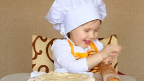 De grappige baby in de rol van kok kneedt deeg stock video
