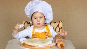 De grappige baby in de rol van kok kneedt deeg stock videobeelden