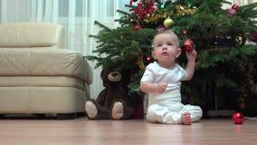 De grappige baby zit onder Kerstboom en speelt met decoratie, kind het kruipen stock videobeelden