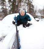 De grappige babyjongen maakt autobonnet van sneeuw schoon Royalty-vrije Stock Foto's