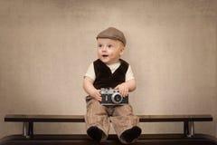 De grappige babyreiziger met een retro camera royalty-vrije stock foto's