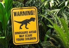 De grappige berichtraad toont dinosaurus in groen bos stock foto's