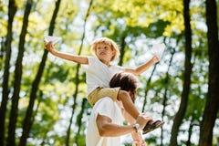 De grappige blonde jongen met zijn vader gekleed in de witte t-shirts is in het park De jongen zit op de schouders van de vader royalty-vrije stock afbeelding