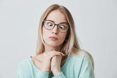 De grappige grappige blondevrouw kruist ogen, pruilt lippen, maakt grimas, foolishes na de hele dag van het bestuderen Clueless w Stock Fotografie