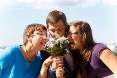 De grappige bruidegom met moeder en de zuster eten boeket van bloemen Stock Afbeeldingen