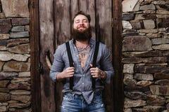 De grappige brutale mens met een baard en tatoegeringen op zijn handen gekleed in modieuze vrijetijdskleding stelt op de achtergr royalty-vrije stock foto