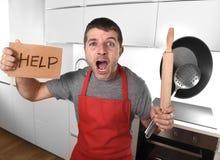 De grappige doen schrikken pan dragende schort van de mensenholding bij keuken die om hulp vragen Royalty-vrije Stock Afbeeldingen