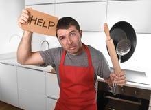 De grappige doen schrikken pan dragende schort van de mensenholding bij keuken die om hulp vragen Royalty-vrije Stock Afbeelding