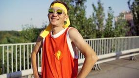 De grappige dunne buitenissige mens is gelukkig na opleiding in het stadspark stock video