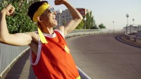 De grappige dunne buitenissige mens is gelukkig na opleiding in het stadspark stock videobeelden