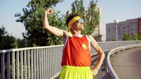 De grappige dunne buitenissige mens is gelukkig na opleiding in het stadspark stock footage