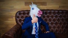 De grappige eenhoorn in elegant kostuum zit op bank als een werkgever en het tonen van gebaar stock foto