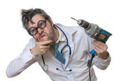 De grappige en gekke arts lacht en houdt zaag op whit in hand Royalty-vrije Stock Fotografie