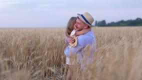 De grappige familiespelen, de mens en een meisjes gelukkige familie spelen speels op het gebied van rijpe tarwe tegen de blauwe h stock video