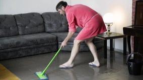 De grappige gebaarde mens in een roze badjas wast betegelde vloer stock video
