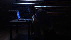 De grappige grappige hakker begaat een cyberaanval met laptop en een kanon in zijn handen stock video