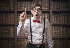 De grappige jonge mens nerd met vinger heeft omhoog een idee stock afbeelding