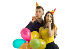 De grappige jonge paar het vieren verjaardag met kegels op hun hoofden houdt gekleurde ballen en slaghoornen Stock Fotografie